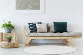 pflanze auf hocker nahe beige sofa mit kissen im wohnzimmer mit weißen runden bö und silber malerei