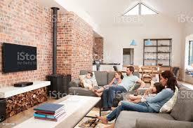 familie sitzen auf sofa in offenes wohnzimmer vor dem fernseher stockfoto und mehr bilder 18 23 monate