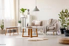 echtes foto einem beige sofa mit kissen und eine decke stnading vor einem tisch und unter einer le in einem wohnzimmer interieur mit pflanzen