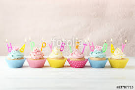 Birthday cupcakes with candles on white wooden background