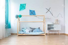 weißer schrank neben diy bett mit blauer bettdecke an der wand mit blauen drachen im schlafzimmer des jungen
