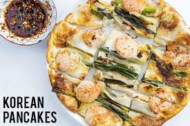 Scallion Prawn Korean Pancake On A Plate And Small Bowl Of Dipping Sauce
