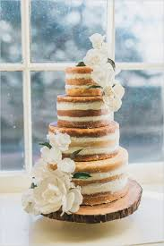 Naked Wedding Cake With White Flowers And Frosting