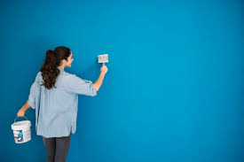 Woman Painting Blue Wall Free Photo