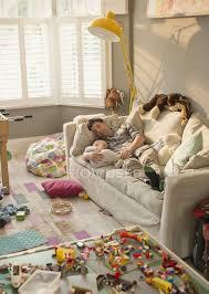 erschöpfter vater und kleiner sohn schlafen auf sofa in