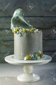 Rustic Style Wedding Cake Decorated With Stone And The Top Of Moss