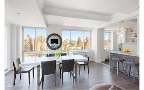 The Dining Room Features Modern Table And Chairs Set On A Hardwood Flooring Lighted By Recessed