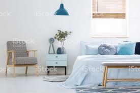pflanze auf schrank zwischen gemusterten sessel und blaues bett im schlafzimmer innenraum mit le echtes foto stockfoto und mehr bilder