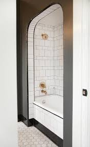 black and white bathroom features an arched alcove filled with