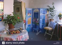 Painted Blue Dufy Style Decorative Folding Screen In Small Dining Room Extension With Houseplant On Circular Table