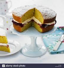 Victoria sponge cake slice cut out on white cake stand white tablecloth blue floral napkin white bone handled knife slice