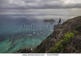 Man Standing At The Edge Of A Cliff Looking Out Over Coast Just Before Sunrise