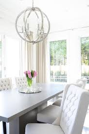 Chic Dining Room Features A Gray Pedestal Table Lined With White Wingback Chairs Illuminated By Polished Nickel Sphere Pendant Surrounded