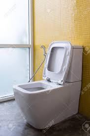 weiß toilette mit wasserspülung und gelbe wand mosaik dekoration im modernen badezimmer interieur zu hause