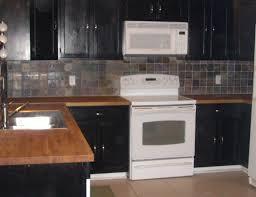 Kitchen Tile Backsplash Ideas With Dark Cabinets by Black Cabinets With Stainless Backsplash And Butcher Block