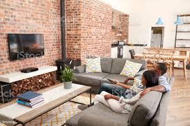 paar auf sofa in offenes wohnzimmer vor dem fernseher sitzen stockfoto und mehr bilder afrikanischer abstammung
