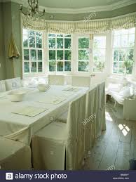 weiße belegabdeckungen auf stühlen in creme land esszimmer