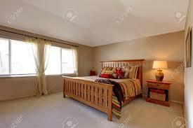 lagre schlafzimmer mit holz bett und nachttisch mit stiel rot grün und gelb betten