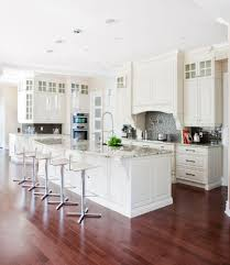 A Rich Red Hardwood Floor Contrasts Beautifully With The White Cabinetry And Marble Countertops Of This