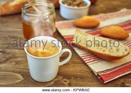 Sweet Honey In Glass Jar And Warm Coffee Bread Cake On A Rustic Tablecloth