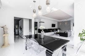 luxuus schwarz und weiß esszimmer mit schwarzer tisch und geist stühle offenes wohnzimmer im hintergrund
