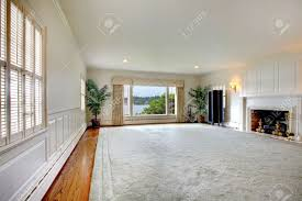 große leere wohnzimmer mit riesigen teppich kamin und blick auf den see