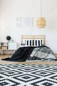 schwarz weiß muster teppich in minimalem schlafzimmer