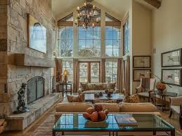 Interior Decoration Classic Living Room With Brown Sofa Under Vintage Chandelier On Cathedral Ceiling Also Stone Rustic Fireplace And Clear Glass Table