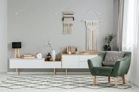 grüner sessel auf gemustertem teppich im hellen wohnzimmer interio foto bialasiewicz auf envato elements