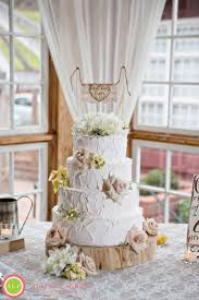 A Rustic Wedding Cake Decorated On The Top Layer With Pink Peonies Small Clusters Of