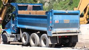 Blue Kenworth Dump Truck Driving In And Dumping His Load Of Dirt ...
