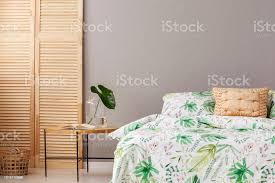 echtes foto runder nachttisch mit aufgeschlagene buch und monstera deliciosa blatt im glas vase stehen durch das doppelbett mit gold kissen und