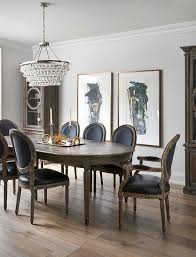 Side By Black And Gold Abstract Art Piece Hang On A White Wall Between Tall Glass Cabinets Behind An Oval French Dining Table Surrounded