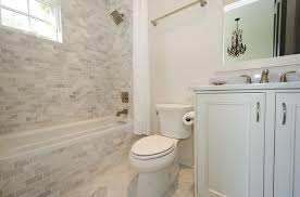 marble subway tiled tub with white shower curtain transitional