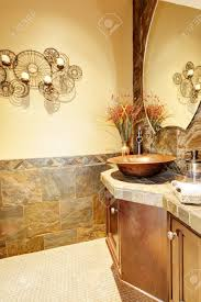 spüle mit holzgehäuse und steinfliesen in dem kleinen badezimmer