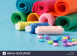 sewing supplies colored threads colored pieces of cloth needles