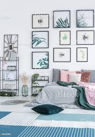 grünes kissen auf den boden mit blauen und weißen teppich innen helle schlafzimmer mit doppelbett gestellt zwei metallracks mit pflanzen und