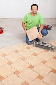 worker laying floor tiles on concrete surface stock photo image