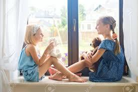 deux jolies filles tout petits européens assis près d une fenêtre