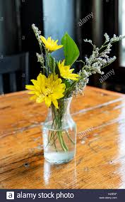 Glass Bud Vase With Yellow And White Flowers On A Rustic Wooden Table Sunlight Streaming In Through The Window
