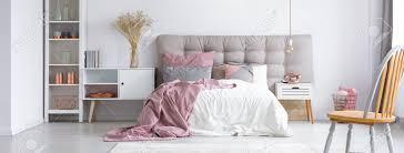 moderne trendige möbel in einem gemütlichen minimalistischen schlafzimmer mit kupfer accessoires und pastellrosa akzenten