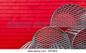 an display of decorative lobster traps sit against a red wall of a