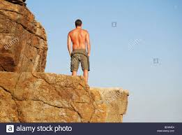 Man Standing On Cliff Edge Looking Out To Sea