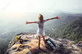 Young Woman Standing With Raised Hands Backpack On Cliffs Edge And Looking Into A Wide