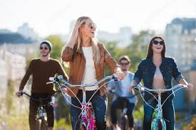 Beautiful Young Smiling Woman Riding Bicycle And Looking Away While Her Friends In The Background Photo By Gstockstudio