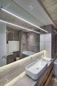 modernes badezimmer mit texturierten fliesen und einer holzdecke es gibt ein weißes waschbecken auf dem gestell wasserhahn hölzerne schließfächer