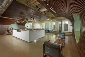 The Reception Area Features Walnut Wood Strips That Travel Up Wall And Curve Across Ceiling Over Desk Offices
