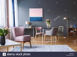 rosa sessel in geräumigen grau esszimmer interieur mit
