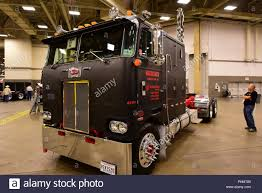 A Dark Peterbilt Cabover Semi Truck Is Displayed At The 2018 Great ...