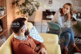 junges paar in ihrem wohnzimmer im gespräch stockfoto und mehr bilder arbeiten zuhause